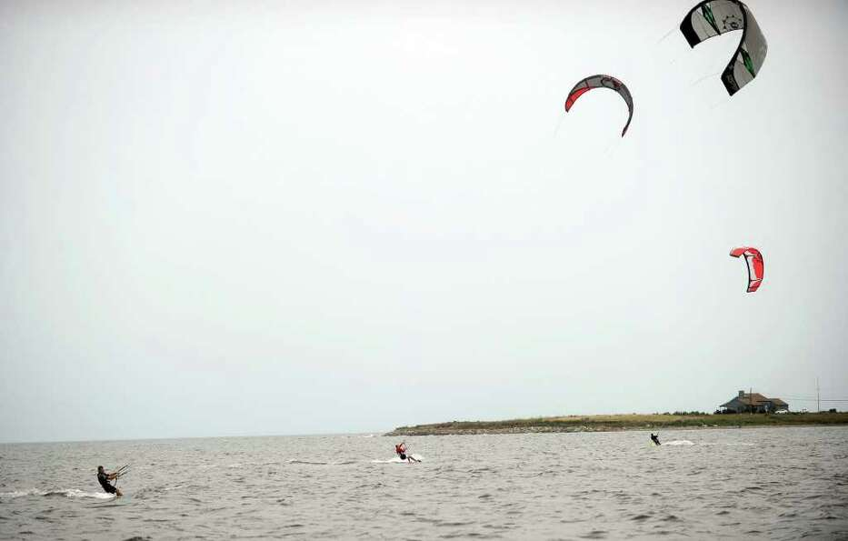 Kitesurfers, who said they were hoping for strong winds in the wake of Hurricane Earl, surf while di