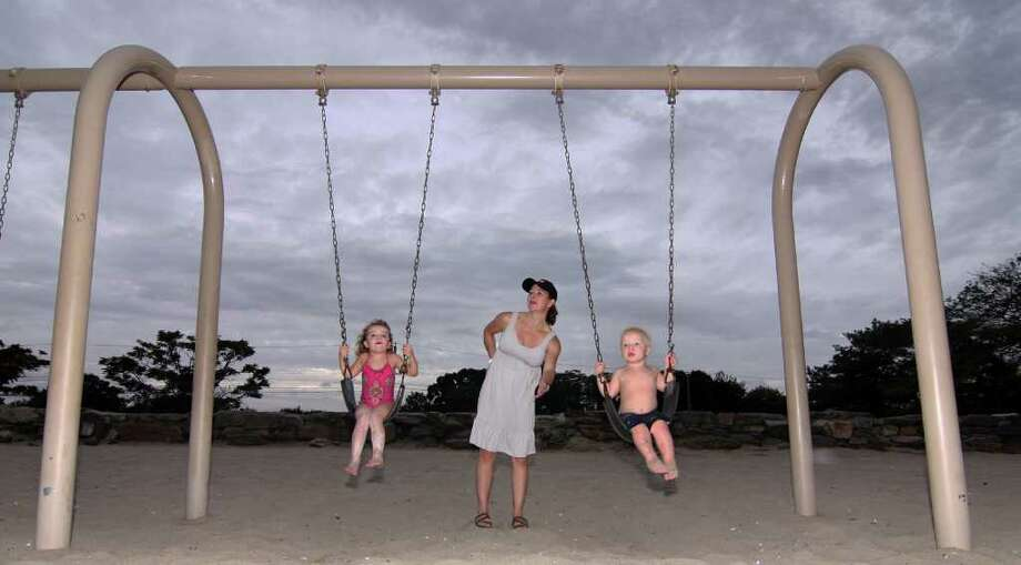 The brunt of Hurricane Earl decided not to pummel Connecticut like predicted on Friday, September 3, 2010. Penfield Beach in Fairfield, Conn., brought out many people to enjoy the water and beach even though winds and waves were high.  Here, Paula Cunningham, of Fairfield, pushes her children Makayla, 4, left, and Thomas, 1, on the swings on the beach as the storm clouds hover over them. Photo: Christian Abraham / Connecticut Post