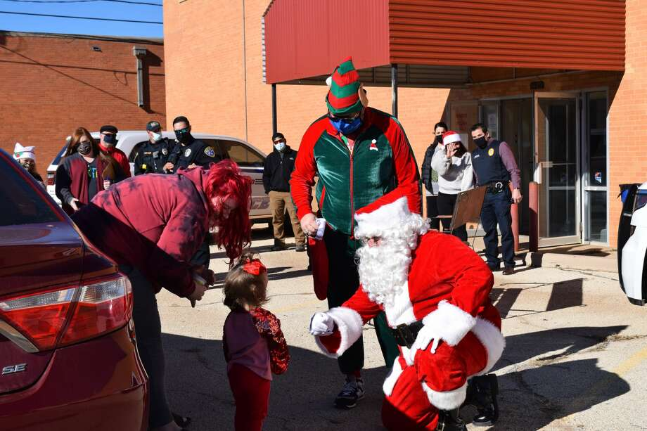 Santa Claus (who knows Plainview ISD Officer Amos Rodriguez well) and an elf (who held up his end of a dare for Kiwanis member J. Patrick Manning) greet a child at the sixth annual Christmas With Cops event hosted by the Plainview Police Department. Photo: Ellysa Harris/Plainview Herald