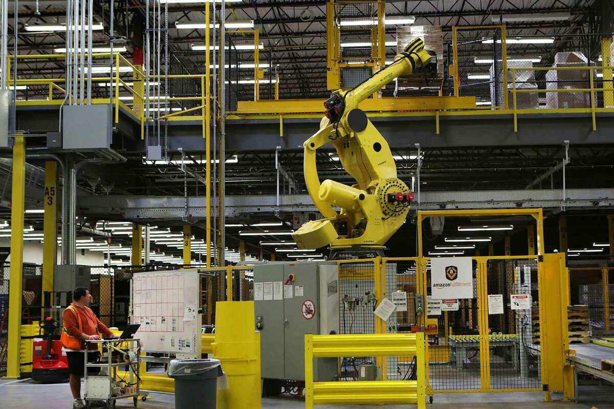A mechanical arm called Robo-Stow lifts a pallet of goods to an upper shelf at Amazon's fulfillment center in Schertz. The company is opening two fulfillment centers in San Antonio, as well as a delivery station.