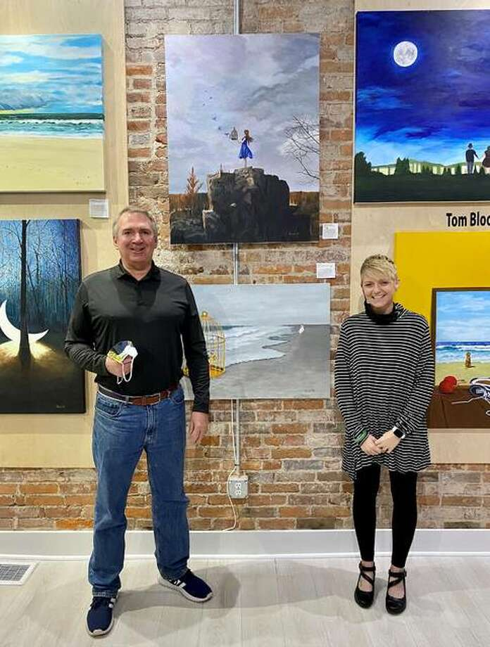"""Artist Tom Blood and gallery owner/curator Brooke Piepert stand in front of the painting, """"Happiness Released,"""" at Good Weather Gallery in Edwardsville."""