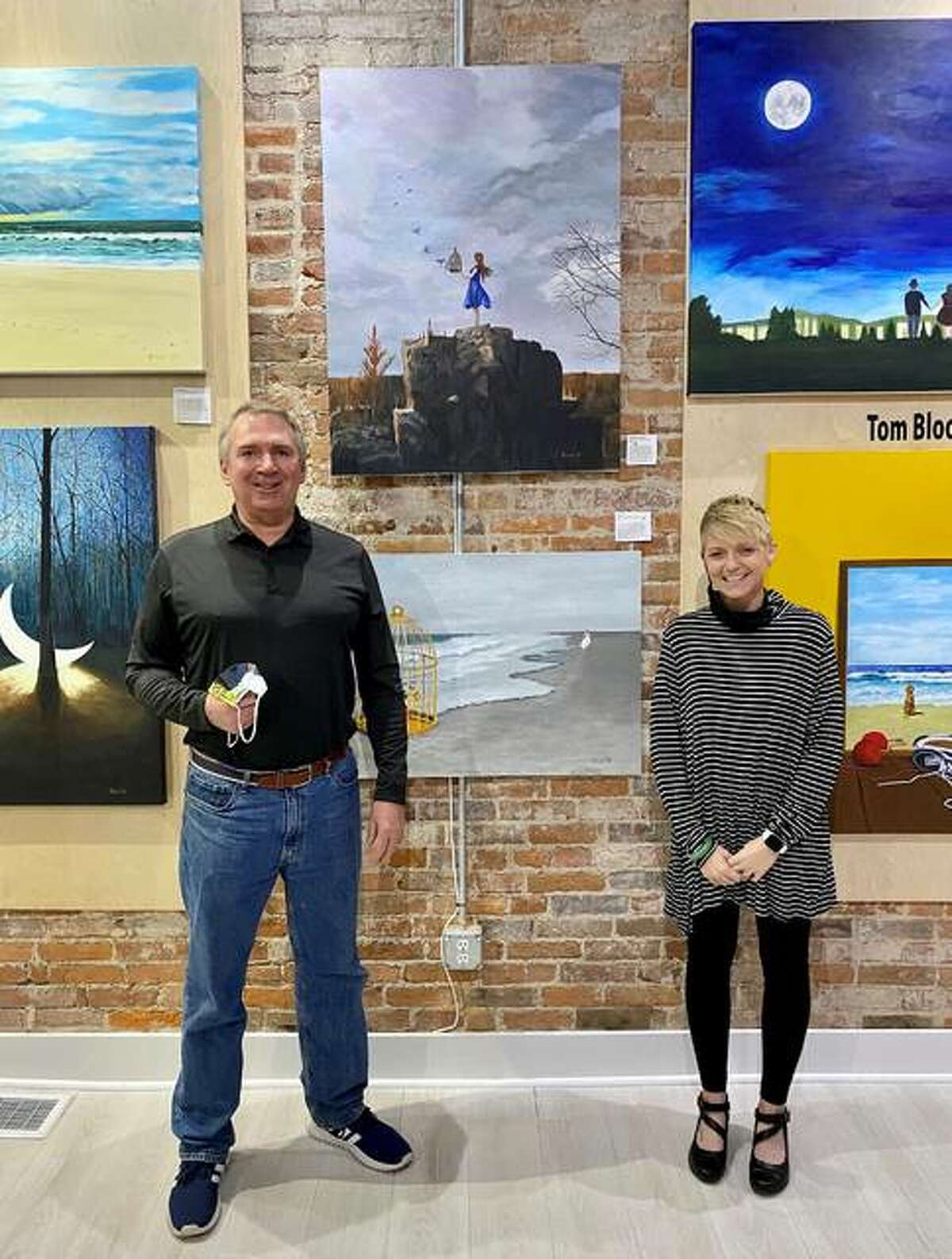 Artist Tom Blood and gallery owner/curator Brooke Piepert stand in front of the painting,