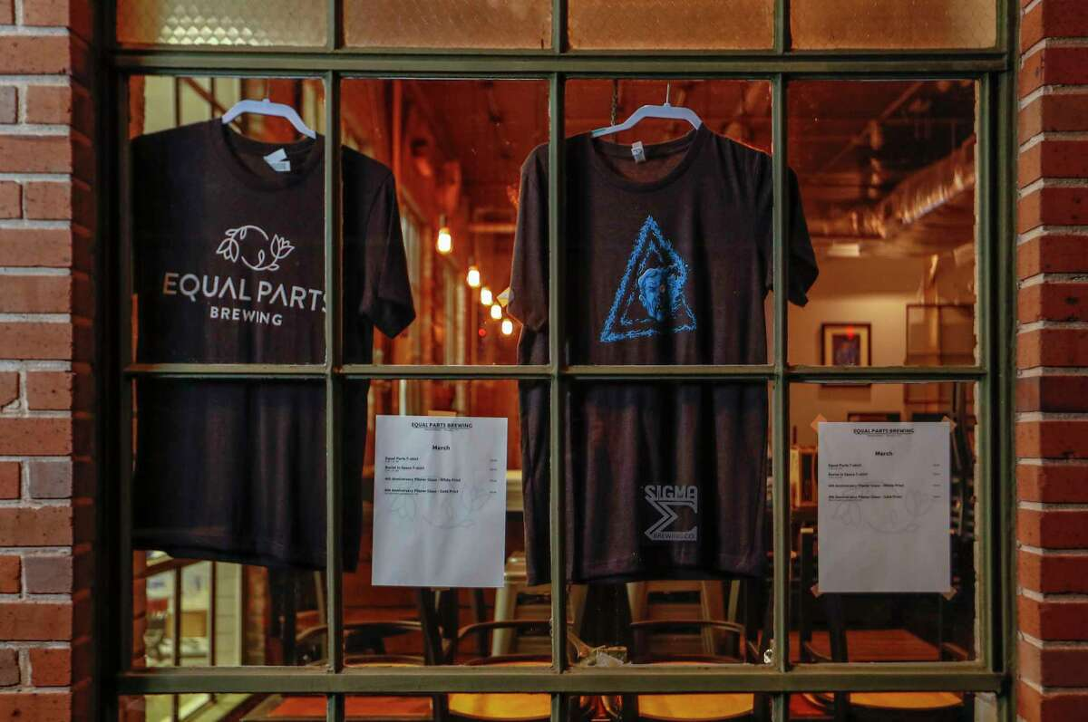 Merch t-shirts hand in the windows at East End-Equal Parts Brewing, 3118 Harrisburg, Thursday, December 17, 2020, in Houston. Formerly known as Sigma Brewing. After four years, and an 8 month taproom closure due to the pandemic, during which they continue to sell out of a
