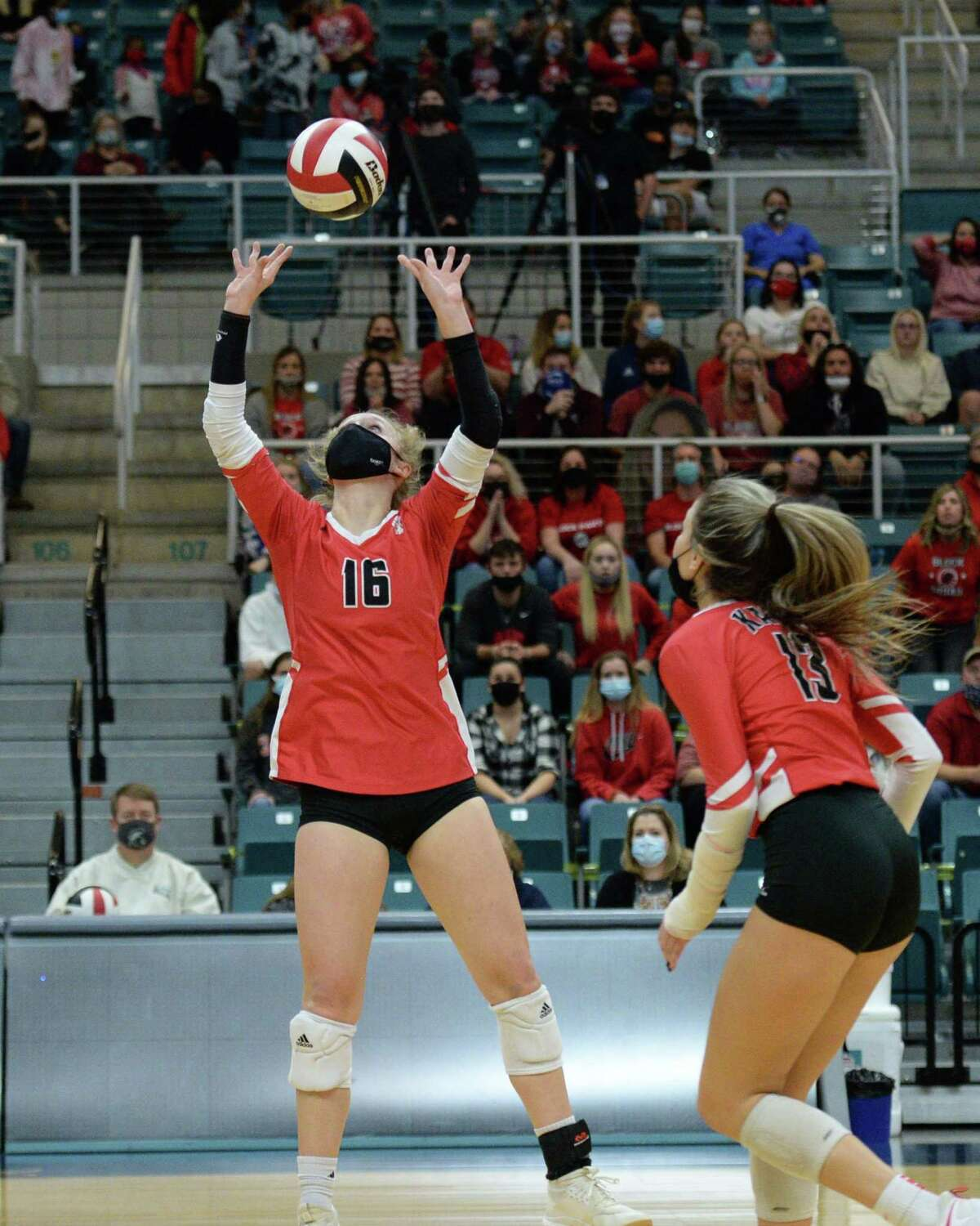 Maddie Waak (16) of Katy sets a ball for Reghan Jones (13) during the first set of the 6A Region 3 Championship game between the Katy Tigers and the Seven Lakes Spartans on Friday, December 4, 2020 at Leonard Merrell Center, Katy, TX.