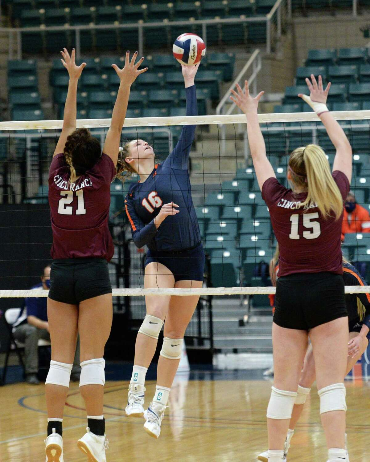 Emma Schroder (16) of Seven Lakes attempts a shot past Kayla Griebl (21) and Camryn Moon (15) of Cinco Ranch during the first set of a 6A-III regional quarterfinal game between the Cinco Ranch Cougars and the Seven Lakes Spartans on Saturday, November 28, 2020 at Leonard Merrell Center, Katy, TX.