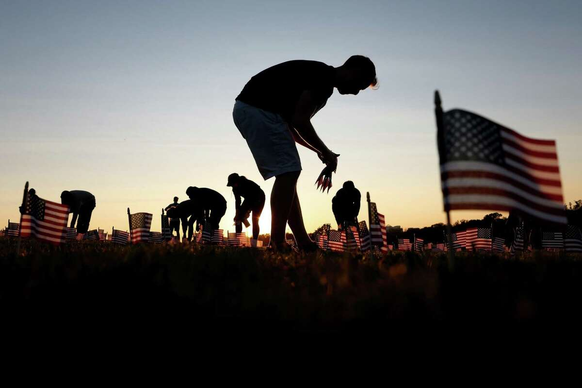 Volunteers with the COVID Memorial Project install 20,000 American flags on the National Mall as the United States crosses the 200,000 lives lost in the COVID-19 pandemic September 20, 2020 in Washington, DC.