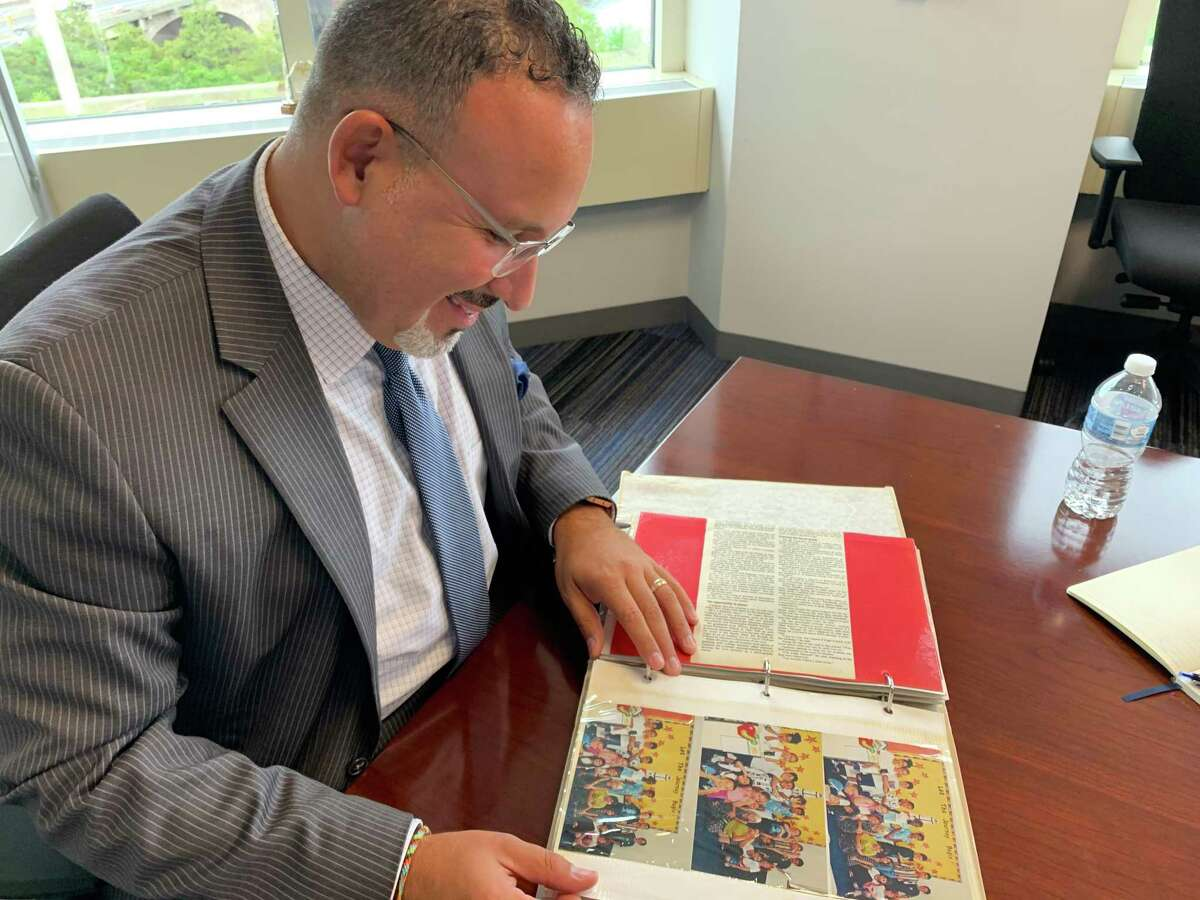 State Education Commissioner Miguel Cardona, at his desk in Hartford in August, 2019, looks over a scrapbook his parents made during his first year of teaching in 1998.