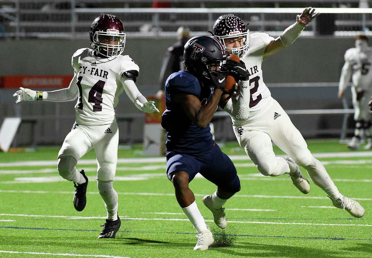 Tompkins wide receiver Mathew Ogunrin, center, catches a pass as Cy-Fair defensive backs Nick Chrest, right, and Keith Ford defend during the first half of a 6A Division I Region III area round high school football playoff game, Friday, Dec. 18, 2020, in Katy, TX.