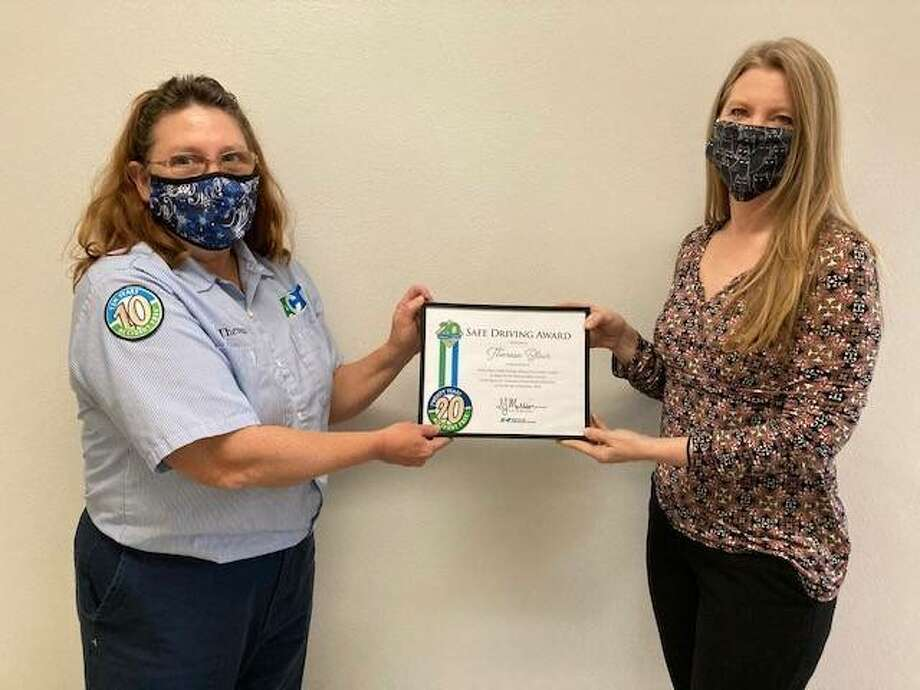 Theresa Blair, Runabout paratransit bus driver, left, receives a certificate for 20 consecutive years of perfect safety while driving a public transportation vehicle from Susan Thomas, Manager of Paratransit Services.