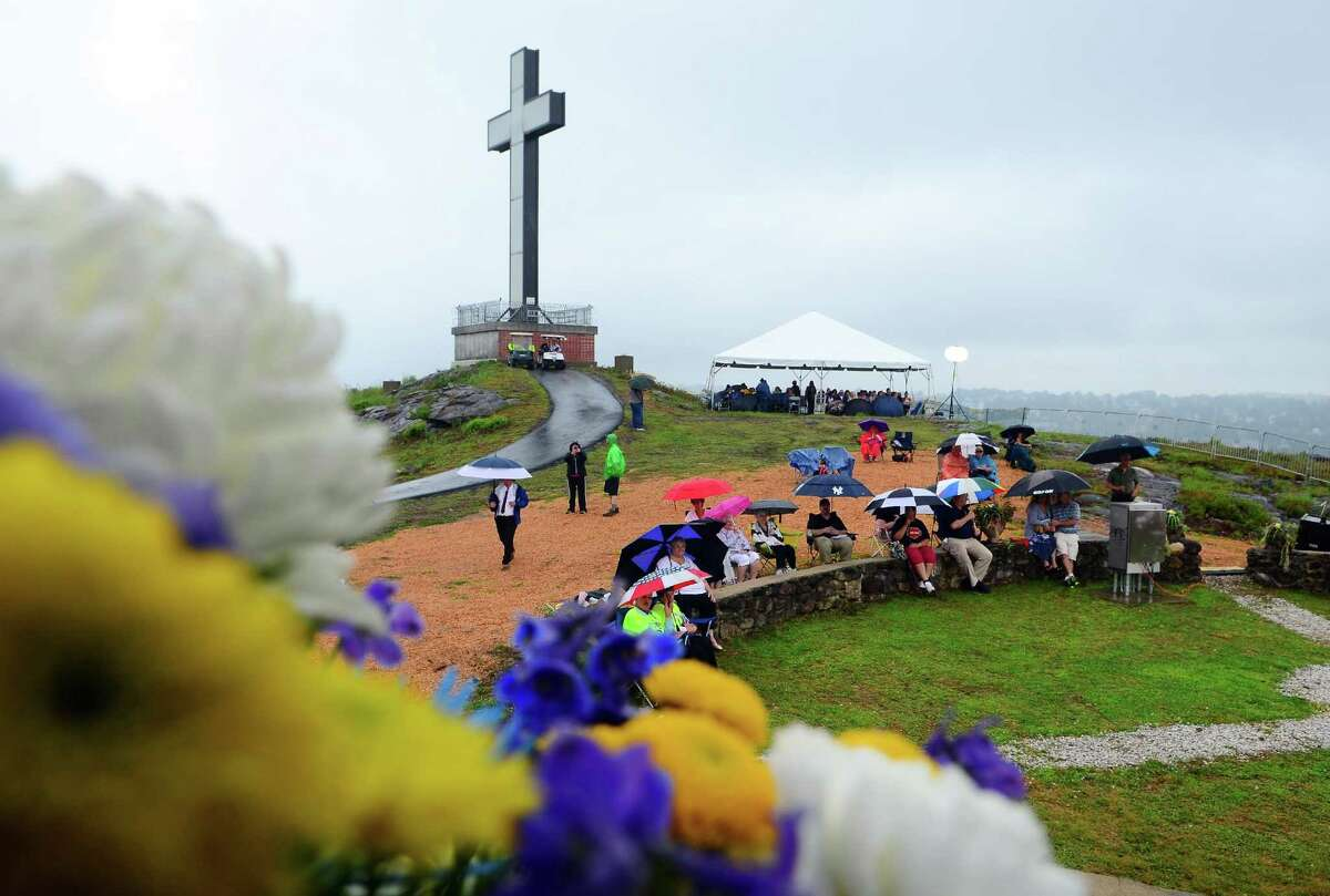 Hundreds of people attend a Mountaintop Mass held at Holy Land USA in Waterbury, Conn., on Saturday Aug. 11, 2018. The mass, led by the Diocese of Hartford Archbishop Leonard P. Blair, was held to celebrate the Legacy of Venerable Father Michael J. McGivney, the founder of the Knights of Columbus. Holy Land USA, a theme park which reopened to the public for the first time since 1984, is being restored and features a 50 foot tall stainless steel cross which is illuminated at night.