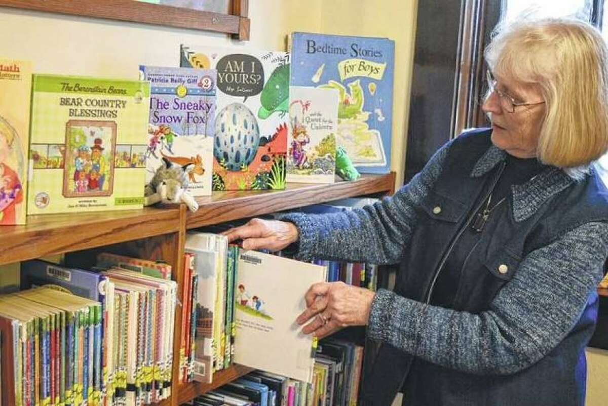 Librarian Darlene Smith stocks books in the children's section of the Winchester Library.