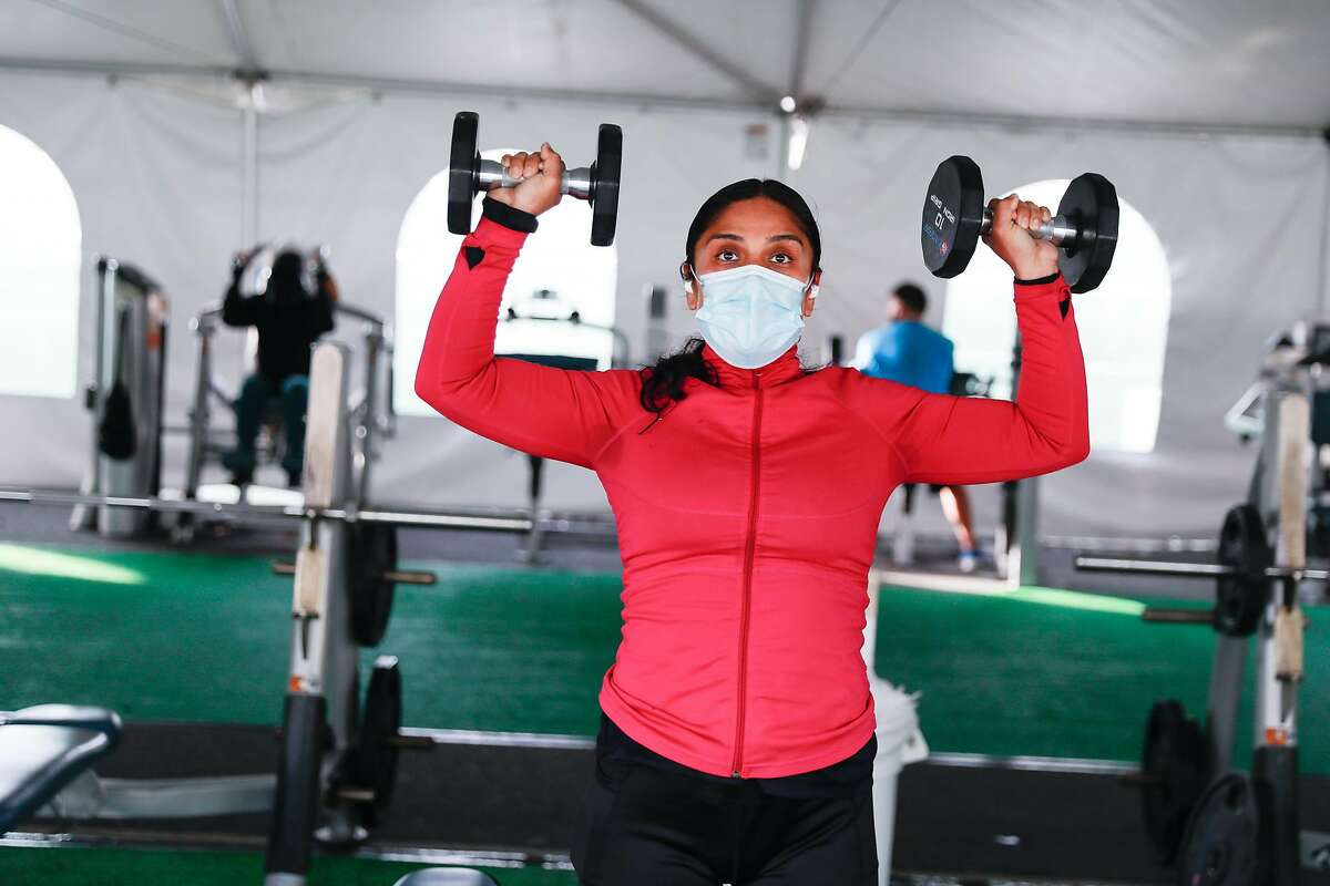 Kat Velasquez exercises in the outdoor tent area at 24 Hour Fitness in Walnut Creek on Wednesday. The company received court approval to exit bankruptcy by the end of the year.