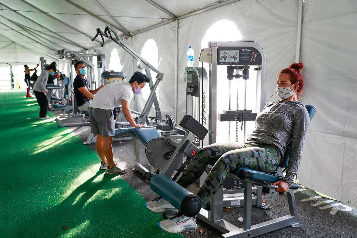 Jocelyne Garcia (right) and others exercise in the outdoor tent area at 24 Hour Fitness in Walnut Creek Wednesday.