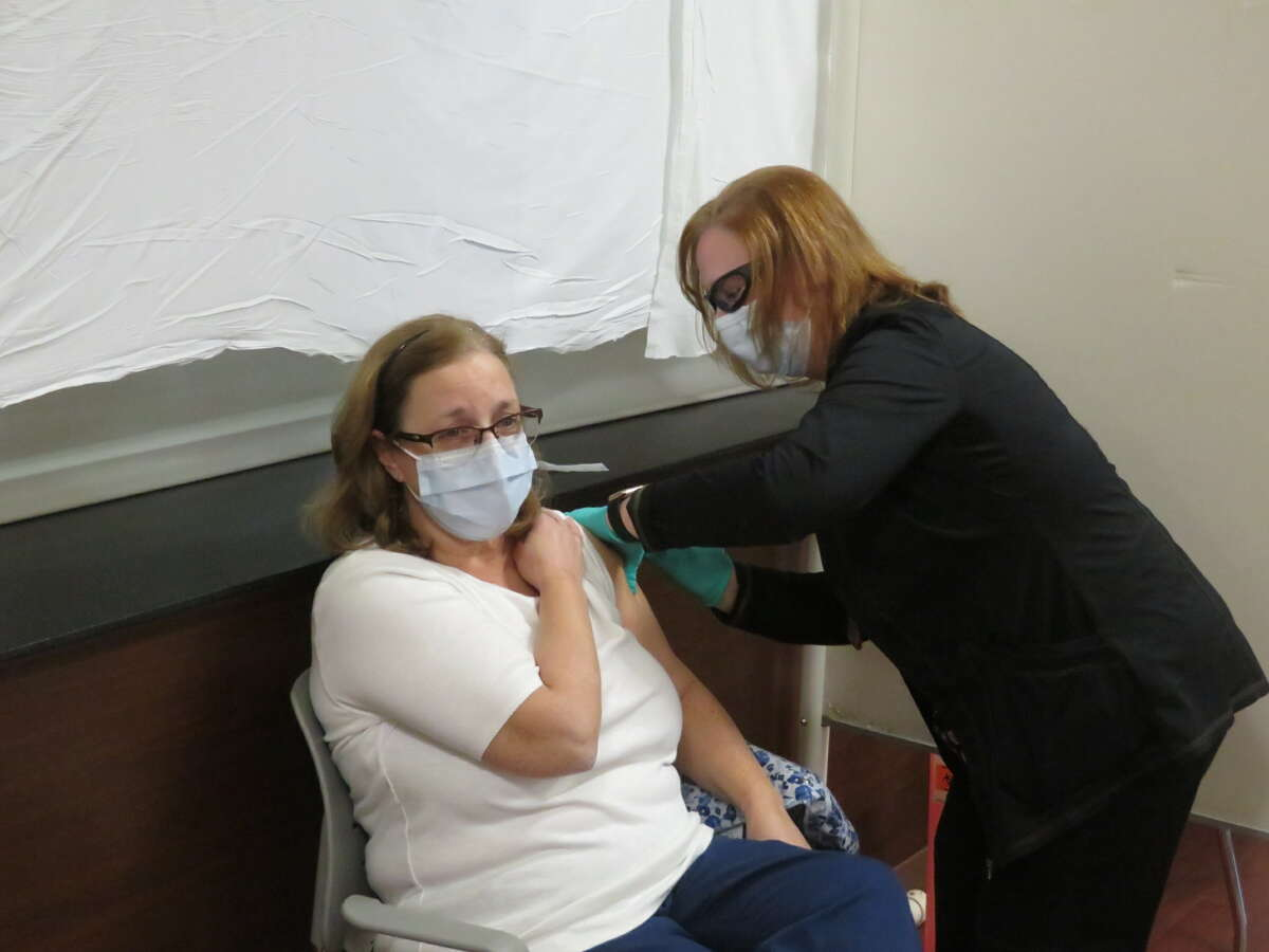 Peggy Rogers, RN, receives a vaccine shot.