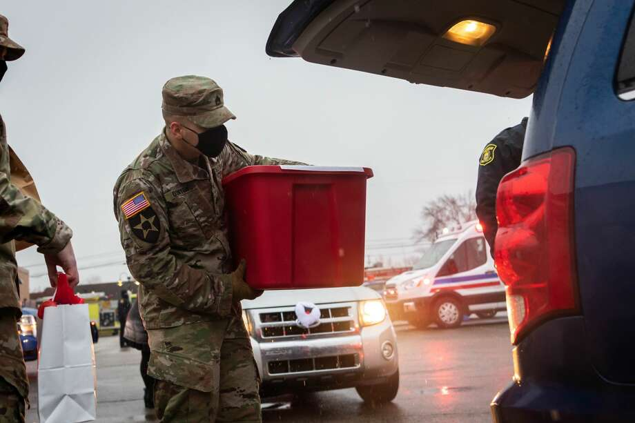 Staff Sargent Gonyon places a bin of Christmas presents into the back of a car for students of Auburn Elementary School Monday, Dec. 21 at Auburn Elementary School. (Cody Scanlan/ for The Daily News) Photo: Cody Scalan For The Daily News