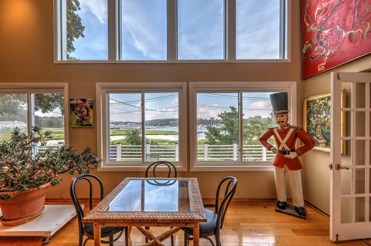 Tall windows in the contemporary at 129 Rogers Avenue, Milford, provide views of Milford Harbor. It's hard to miss the floor-to-ceiling green granite fireplace flanked by built-in bookshelves in the home's library.