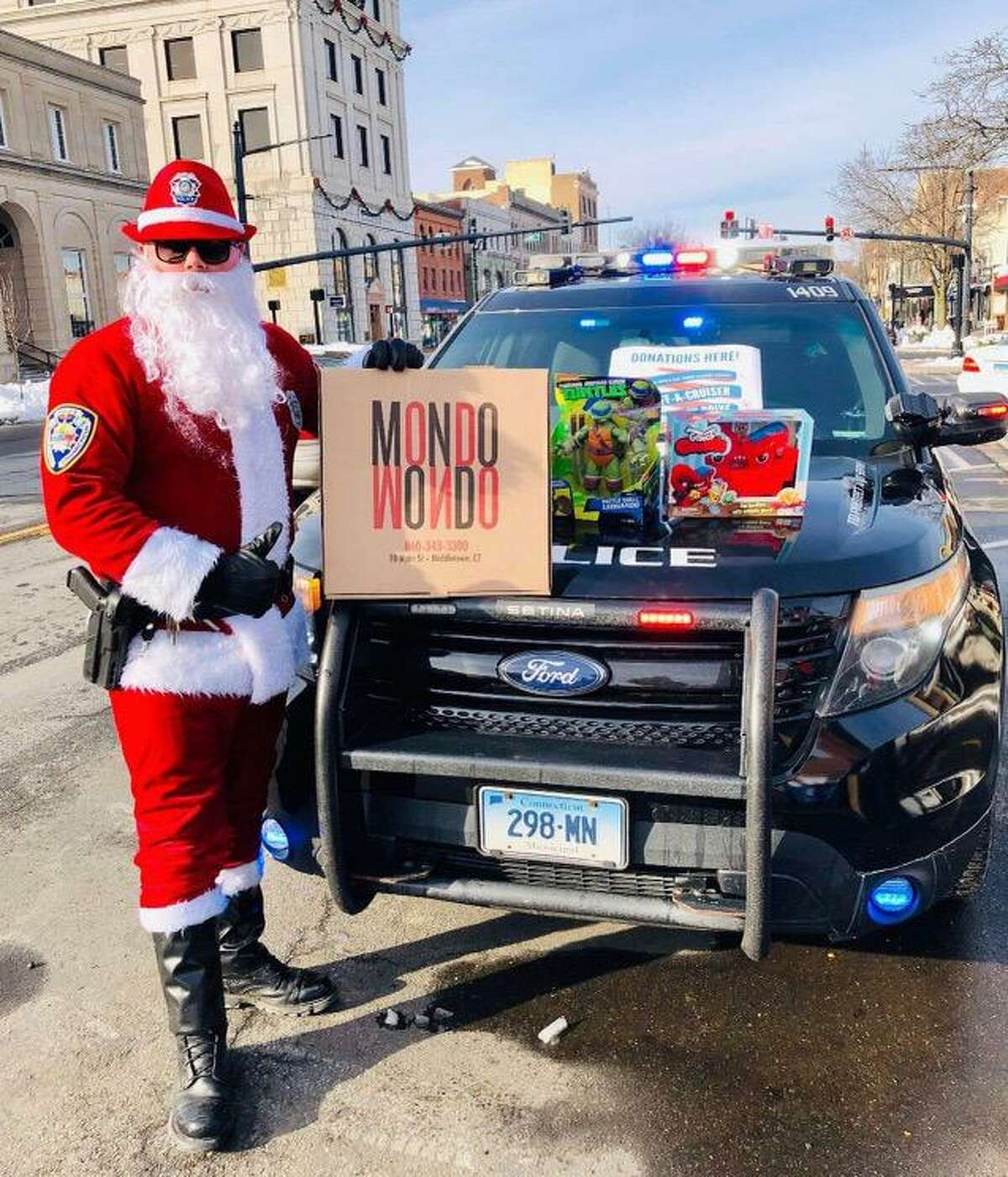 Dressed as Santa, Middletown Police Community Relations Officer Jay Bodell shows off some of the holiday toy donations from the community, and Mondo Pizza, which gave a $60 gift card to a city family in need.