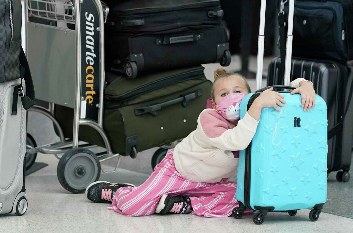 Emma Sisler, 7, sits on the floor as she waits with her family to check in at Hobby Airport Tuesday, Dec. 22, 2020 in Houston.