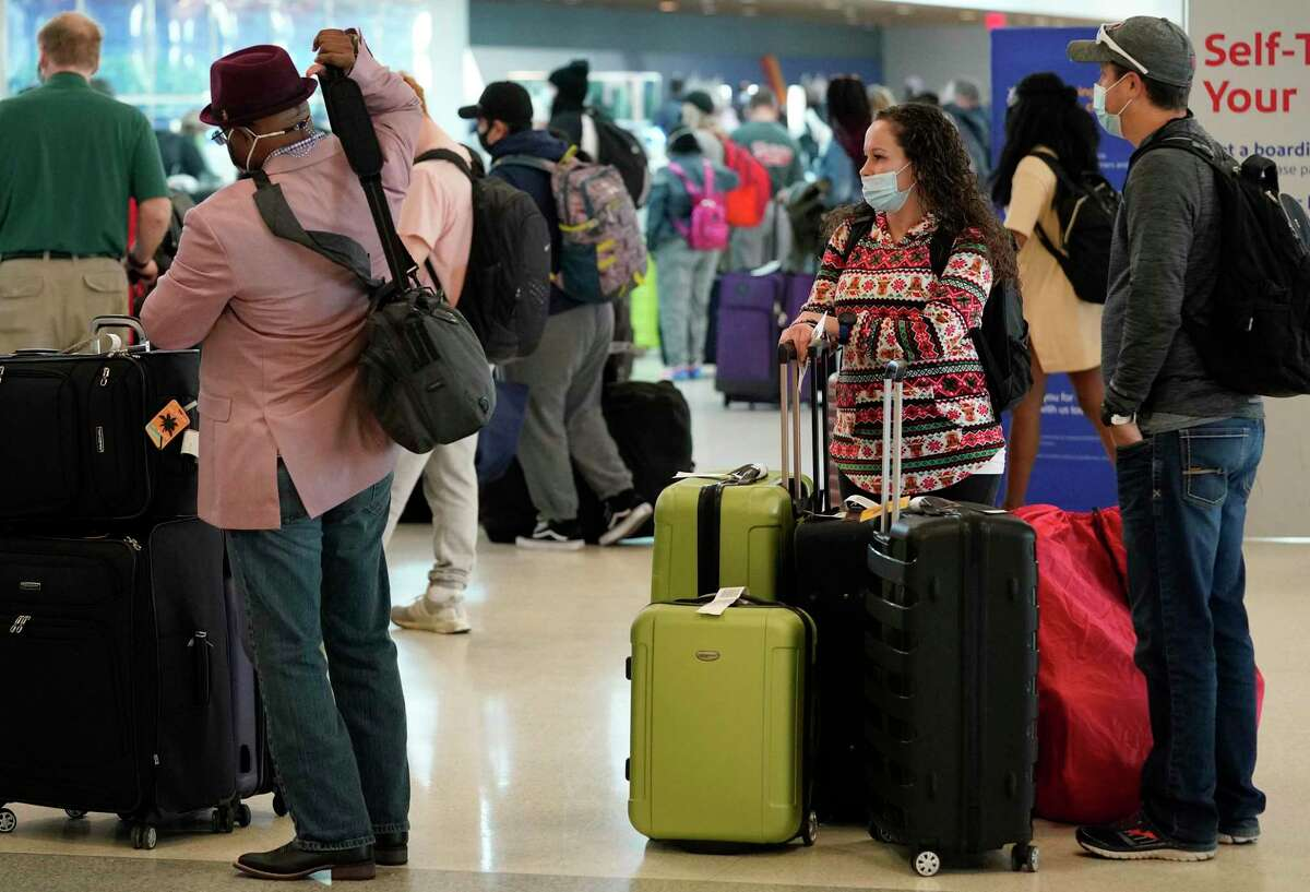 People wait in lines to check in at Hobby Airport Tuesday, Dec. 22, 2020 in Houston.