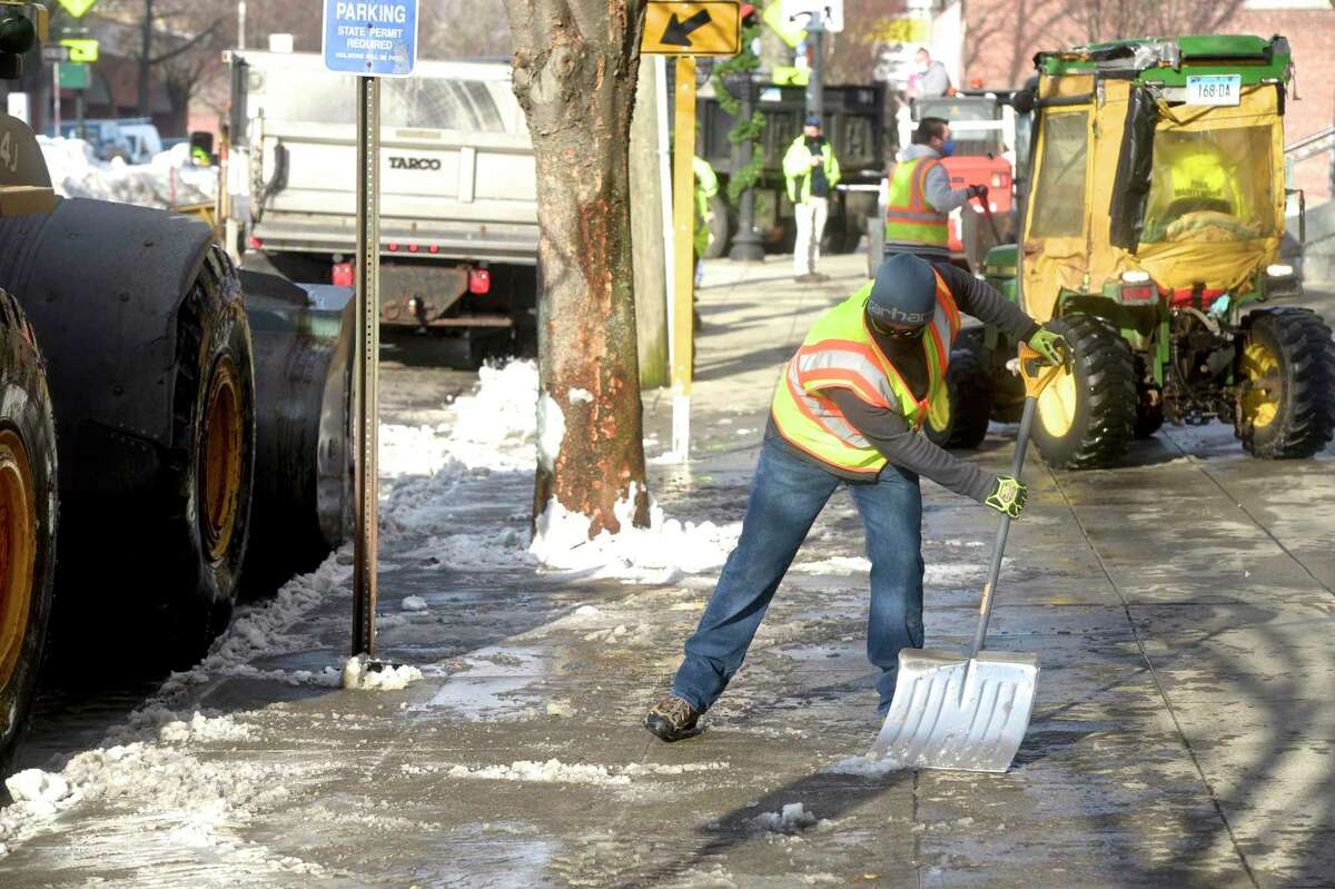 Parks department employee Matthew Reed shovels snow from a sidewalk on Main Street Tuesday morning. DANBURY - Clean-up continues after more than a foot of snow was dumped on the city last week.