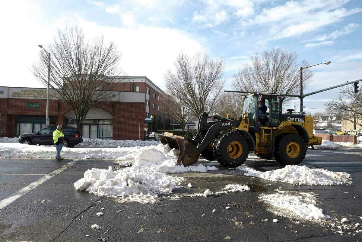 Rick Russo, with the highway department, uses a pay-loader to remove snow from an intersection of Main Street on Tuesday.