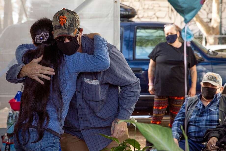 Aileen (who asked to be identified only by her first name) hugs former neighbor Randy Hood, thanking him for saving her life while escaping from a wildfire, as they gather near her temporary trailer alongside former neighbors and fellow fire victims at the Napa Valley Expo Fairgrounds. Photo: Jessica Christian / The Chronicle
