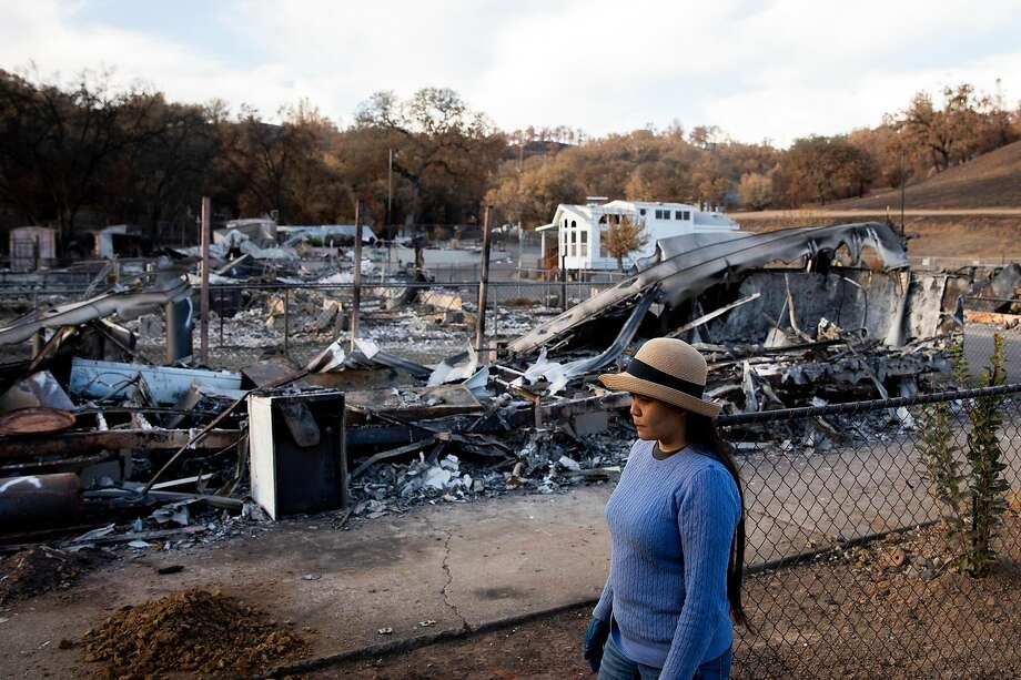 Aileen (who asked to be identified only be her first name) walks past charred remains of neighbor's homes and belongings at the Spanish Flat Mobile Villa. Photo: Jessica Christian / The Chronicle