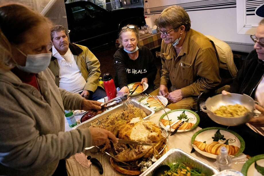 Dorothy Glaros (left) serves her friends and former Spanish Flat Mobile Villa residents Rich Woodard, Michele Quecke, Daniel Davenport and Catalina Tercero an early Thanksgiving dinner at the Napa Valley Expo fairgrounds, where they've been allowed to park their vehicles. Photo: Jessica Christian / The Chronicle