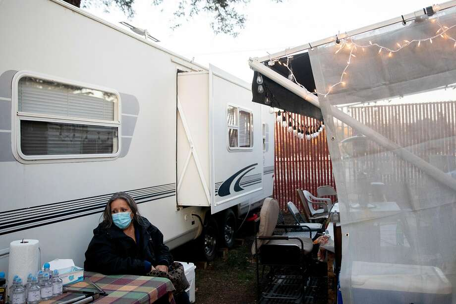 Melinda Dominguez wears a mask while sitting outside of her former neighbor Aileen's trailer at the Napa Valley Expo fairgrounds. Dominguez lost her home at Spanish Flat in the LNU Lightning Complex fires. Photo: Jessica Christian / The Chronicle