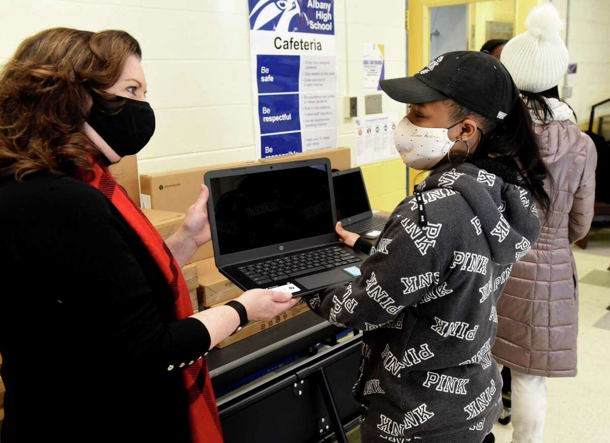 Allison Bashkoff, chief financial officer for the Workforce Development Institute, left, presents a new laptop to Amani Santos, a senior at Albany School taking part in the school's technical education program, during a press conference where the Workforce Development Institute donated 100 laptops to students taking part in Albany High School?•s Abrookin Career and Technical Center programs on Tuesday, Dec. 22, 2020, at the Abrookin Career and Technical Center in Albany, N.Y. Seniors taking career and technical education (CTE) classes will receive the Chromebooks, which they will be allowed to keep. (Will Waldron/Times Union)