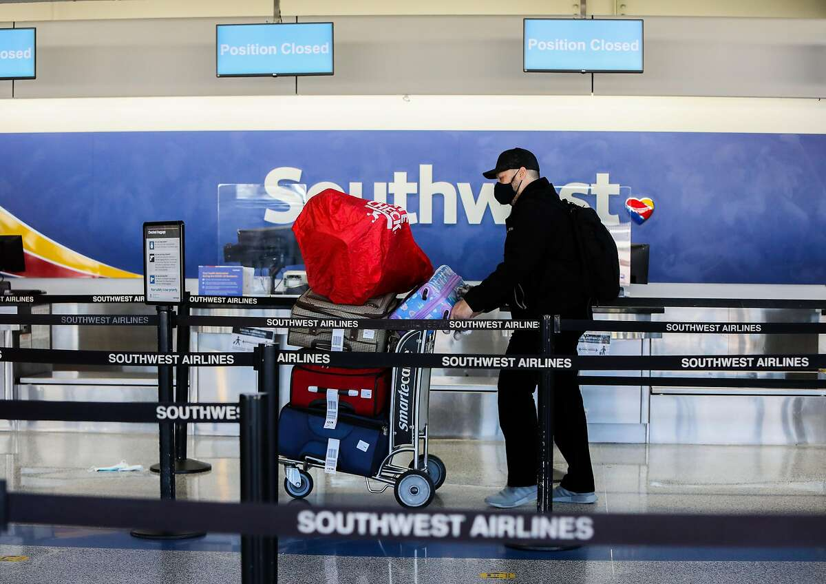 A traveler walks to the Southwest counter at Oakland International Airport on Tuesday, December 22, 2020, in Oakland, Calif. Many folks are still traveling despite coronavirus warnings from health experts.