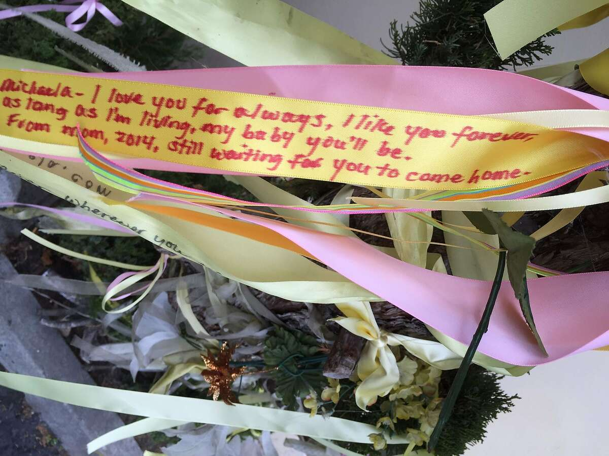 Sharon Murch wrote a message on a ribbon to her missing daughter during a gathering at the Hayward shopping center parking lot where Michaela Garecht disappeared in November 1988.