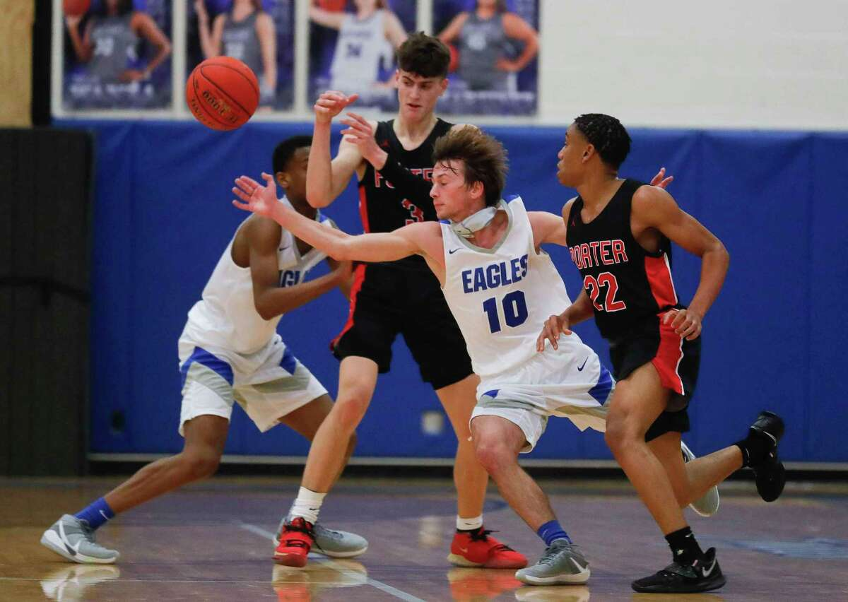 New Caney guard Ethan Brandon (10) tips a pass away from Porter shooting guard Luke Currier (3) during the fourth quarter of a District 20-5A high school basketball game at New Caney High School, Tuesday, Dec. 22, 2020, in New Caney.