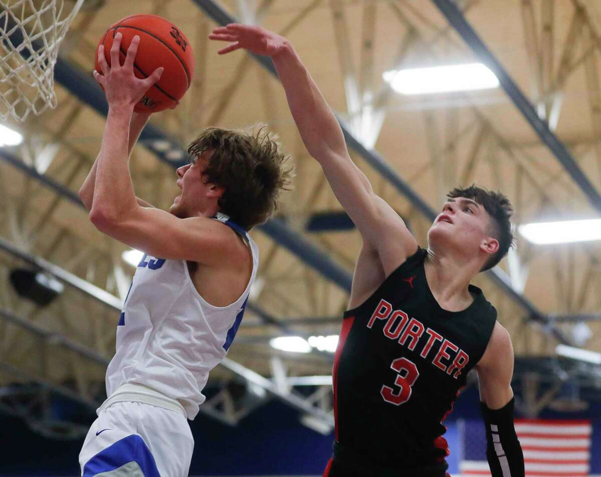 New Caney shooting guard Samuel Brandon (12) drives to the hoop around Porter shooting guard Luke Currier (3) during the fourth quarter of a District 20-5A high school basketball game at New Caney High School, Tuesday, Dec. 22, 2020, in New Caney.