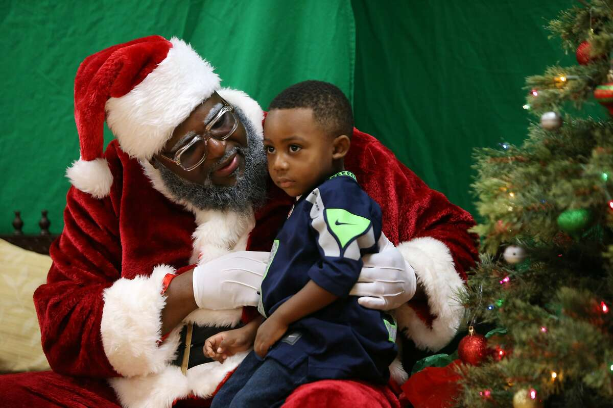 Kaesen Hill, 3, has his photo taken with Santa, aka Chukundi Salisbury, Dec. 16, 2018. The group 100 Black Parents hosted a free Black Santa event at the Langston Hughes Performing Arts Center for kids to have their photos taken with Santa Claus.