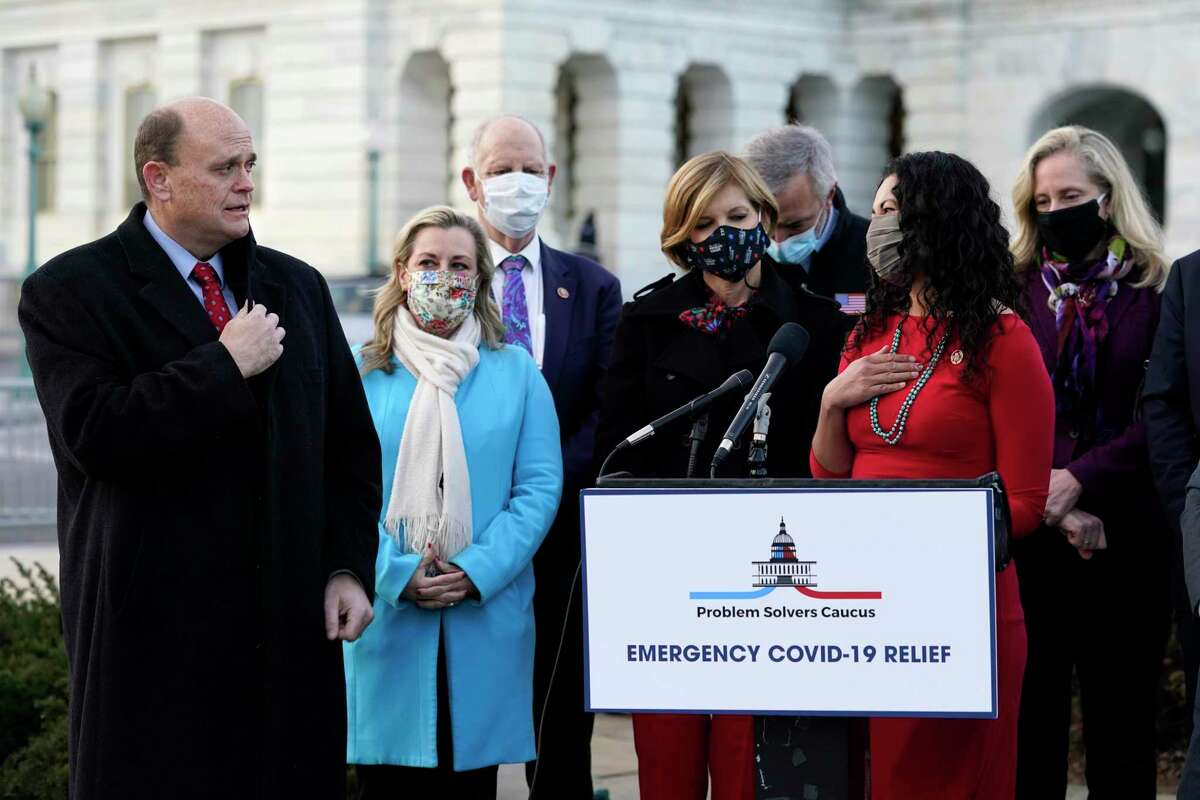 Problem Solvers Caucus co-chair Rep. Tom Reed, R-N.Y., left, tells Rep. Xochitl Torres Small, D-N.M., right in red, how much they will miss her next Congress as their caucus speaks to the media about the expected passage of the emergency COVID-19 relief bill, Monday, Dec. 21, 2020, on Capitol Hill in Washington. Congressional leaders have hashed out a massive, year-end catchall bill that combines $900 billion in COVID-19 aid with a $1.4 trillion spending bill and reams of other unfinished legislation on taxes, energy, education and health care.