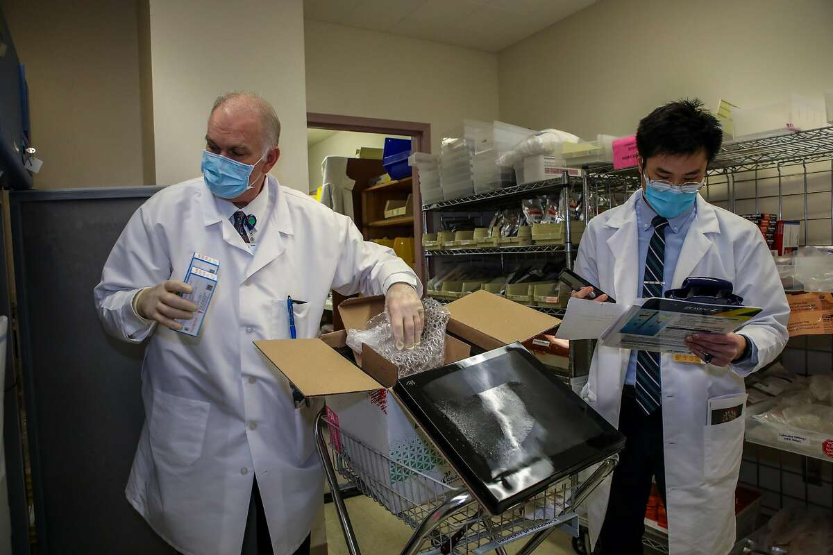 Dr. Sean McElligott, pharmacy director, places boxes containing the Moderna COVID-19 vaccine into a freezer as Dr. Andrew U (right) makes notes at Seton Medical Center in Daly City on Tuesday.