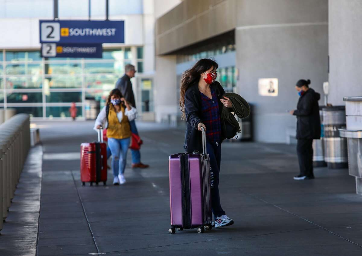 Travelers arrive to Oakland International Airport on Tuesday, December 22, 2020, in Oakland, Calif. Many folks are still traveling despite coronavirus warnings from health experts.