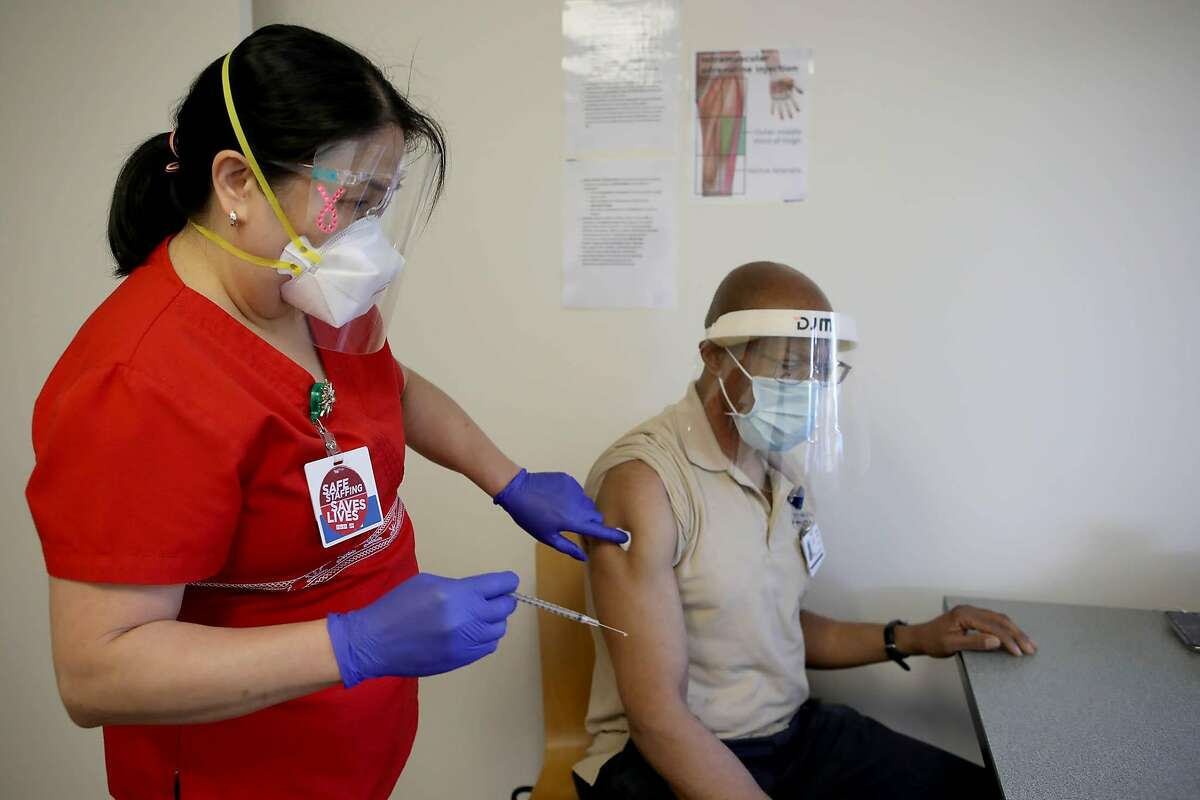 Veronica Avena, RN, inoculates Mark Gilbert, with housekeeping services, with a coronavirus vaccine at Seton Medical Center on Monday, December 21, 2020, in Daly City, Calif.