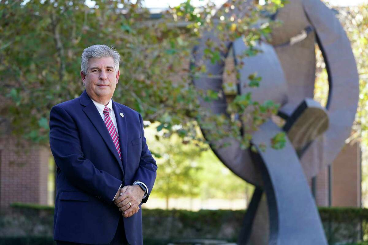"""Armando Colombo, CEO, is shown on the campus of The Menninger Clinic, 12301 Main St., Tuesday, Dec. 8, 2020 in Houston. Shown in the background is John Whitfield's abstract sculpture, """"Vital Balance"""", its title, honors the book by Dr. Karl Menninger of the same name. The sculpture is 21 feet tall and weighed 3,000 pounds."""