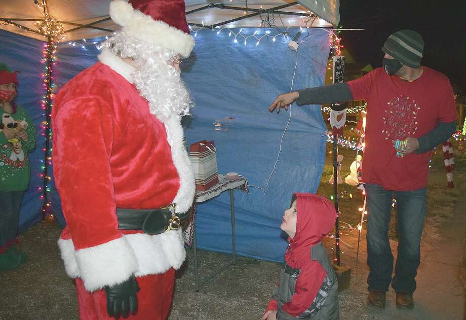Diezel McGee, 4, visits with Santa, who made a stop Tuesday at the home of Brighton McNeece in the 600 block of South Church Street. Photo: Samantha McDaniel-Ogletree   Journal-Courier