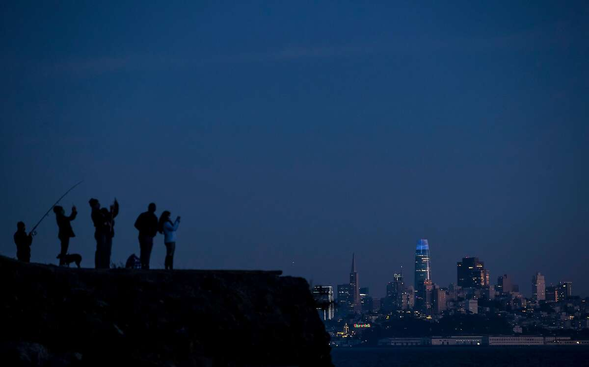 Visitors watch Jupiter and Saturn over the Golden Gate Bridge from Sausalito, Calif., on Sunday, December 20, 2020. The two planets are approaching their