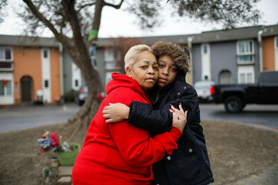 Decynthia Henderson with her son Juliaann Henderson, 13, in front of a memorial for her son Mark Henderson II, who was slain in front of her home in 2018 when he was mistaken for someone else. Photo: Gabrielle Lurie / The Chronicle