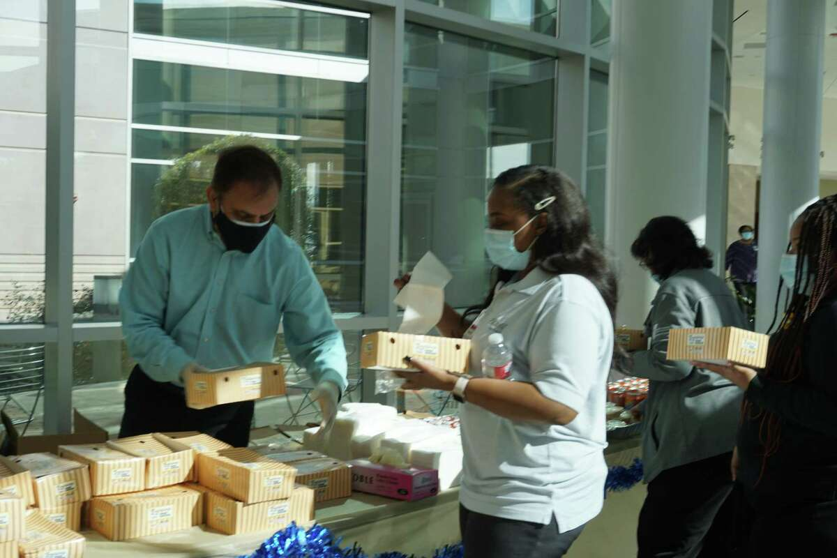 Baig Mohammed, left, owner of Louisiana Famous Fried Chicken, serves lunch to health care workers on Monday, Dec. 21, at Memorial Hermann Sugar Land Hospital.