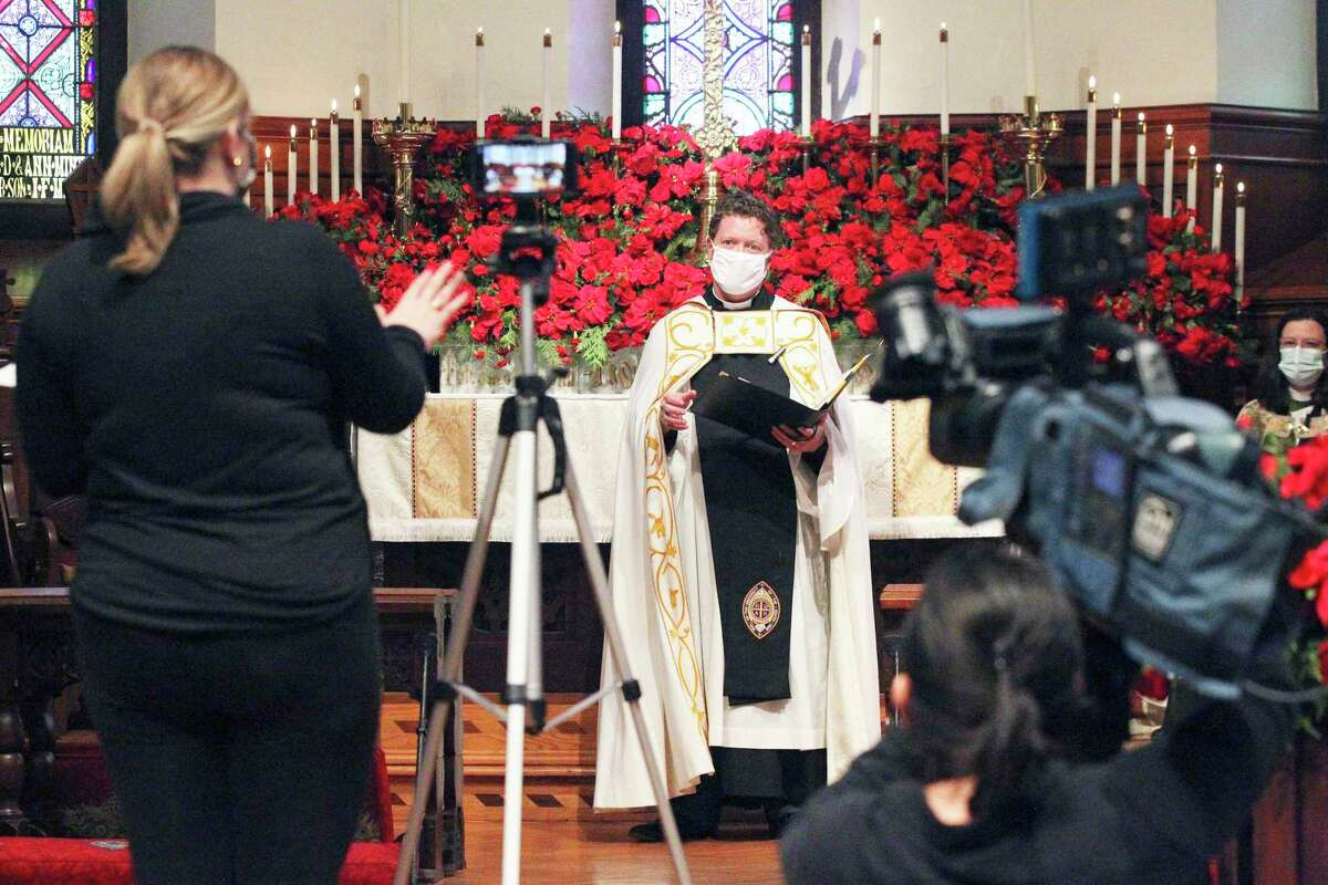 The Rev. Matthew Wise waits for a cue from communications director Rachel Dugger as St. Mark's Episcopal Church recorded its Christmas Day service Tuesday for a virtual presentation.