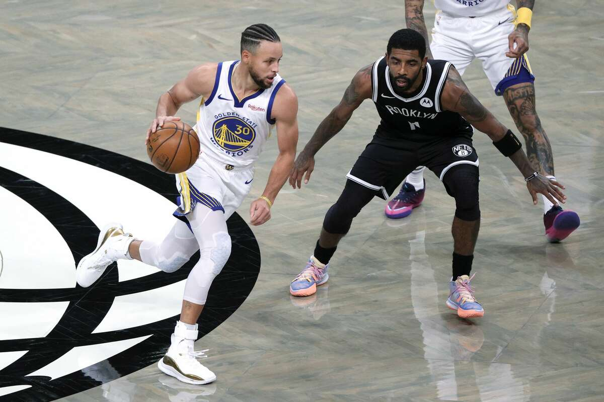 Stephen Curry #30 of the Golden State Warriors dribbles against Kyrie Irving #11 of the Brooklyn Nets during the first half at Barclays Center on December 22, 2020 in the Brooklyn borough of New York City.
