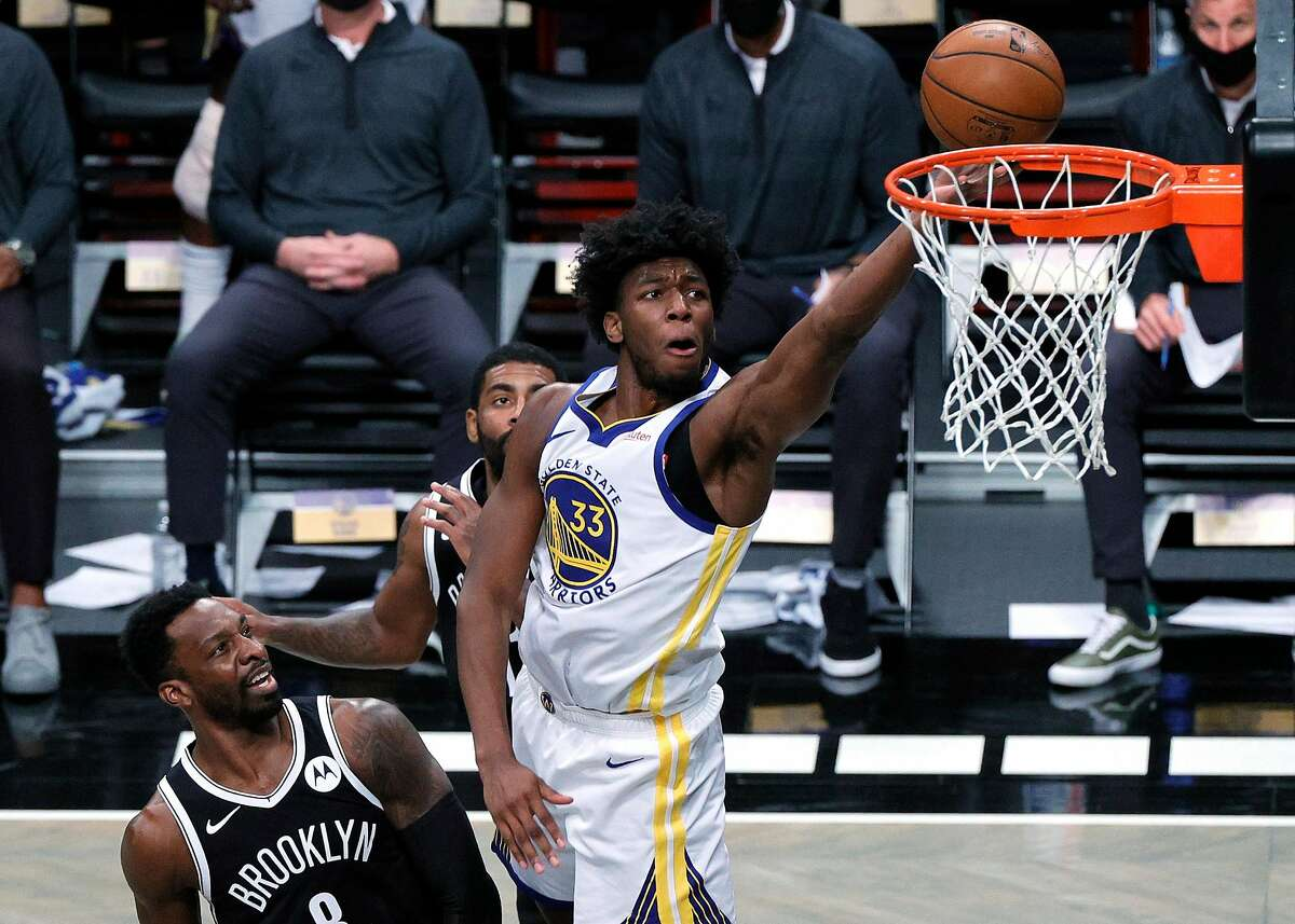 NEW YORK, NEW YORK - DECEMBER 22: James Wiseman #33 of the Golden State Warriors attempts a layup against Jeff Green #8 and Kyrie Irving #11 of the Brooklyn Nets during the first half at Barclays Center on December 22, 2020 in the Brooklyn borough of New York City.