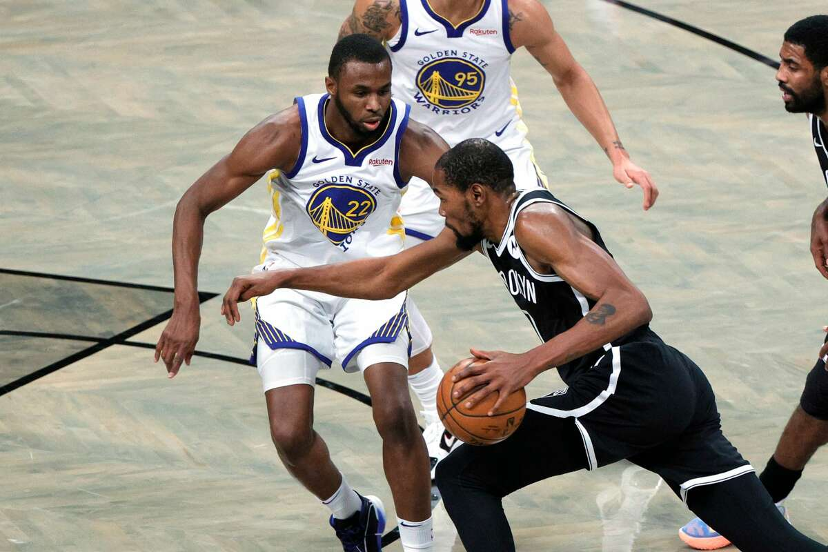 Kevin Durant (7) of the Brooklyn Nets dribbles against Andrew Wiggins (22) of the Golden State Warriors during the first half at Barclays Center on December 22, 2020 in Brooklyn.