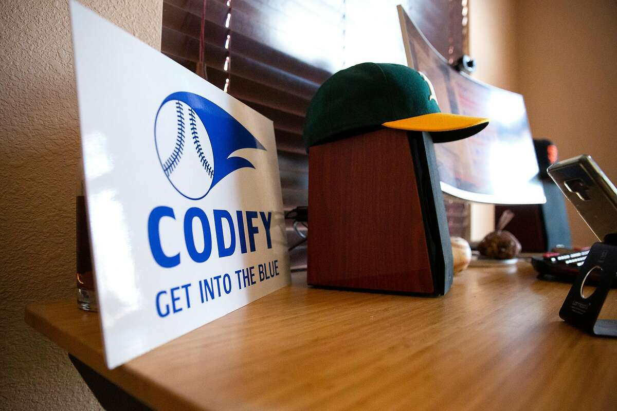 The Codify company sign sits on Michael Fisher's desk along with an Oakland A's and San Francisco Giants hat at his home office in Vacaville on Dec. 15, 2020.
