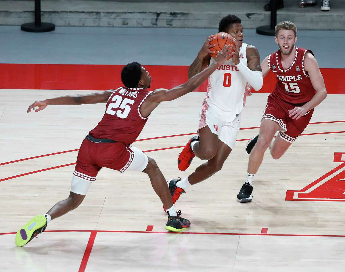 Houston Cougars guard Marcus Sasser (0) works against Temple Owls guard Jeremiah Williams (25) and Brendan Barry (15) during the first half of an NCAA men's basketball game at Fertitta Center, Tuesday, December 22, 2020, in Houston.